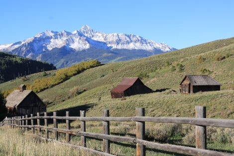 Wilson Peak towers over some barns in Telluride.
