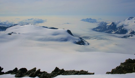 the mighty Bear Glacier flows down into the clouds towards the Gulf of Alaska